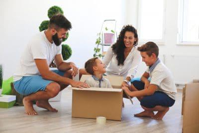 Mann, Frau und ein Junge um ein Kind in Umzugsschachtel versammelt