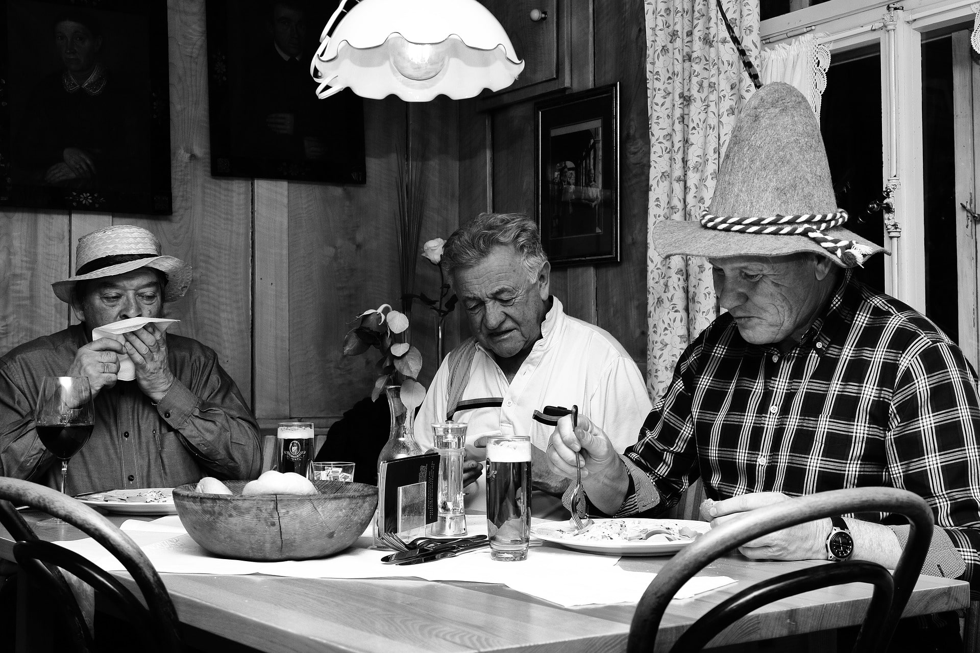 three men with hats sit together at the table and eat