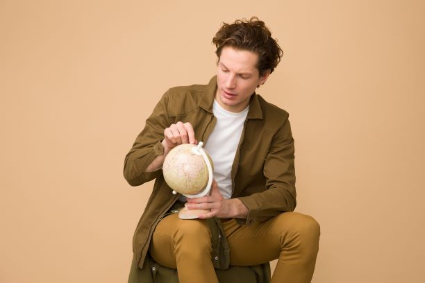 Man with brown suit points sitting on globe