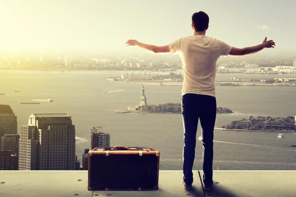 Mann streckt die Arme vor Skyline, neben ihm ein Koffer