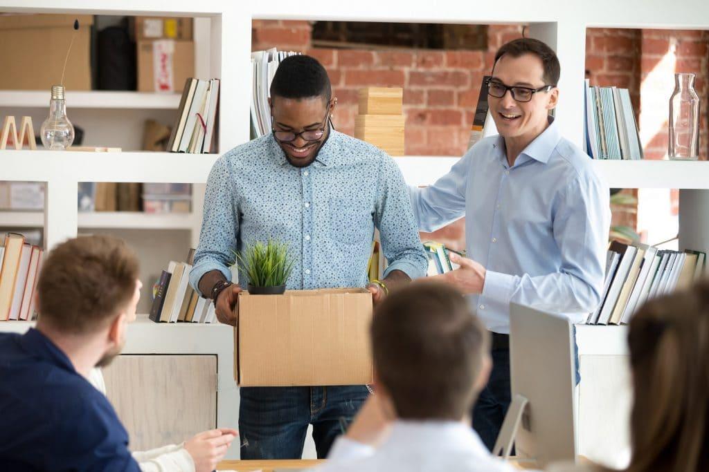 Mann präsentiert einen Schachtel tragenden Mitarbeiter