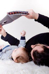 Mann und Baby schauen am Boden liegend in ein Buch