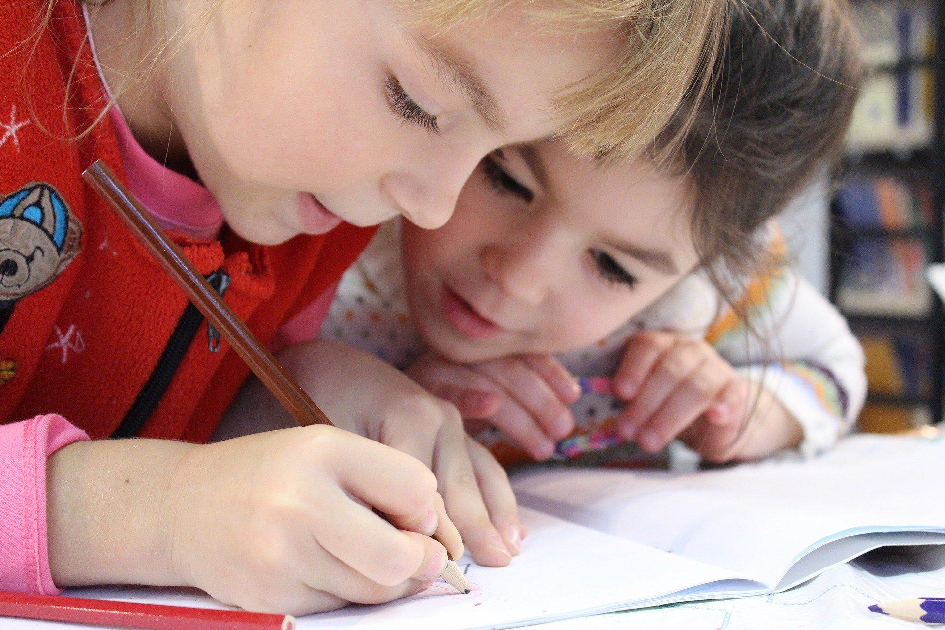 zwei Kinder schreiben in ein Heft